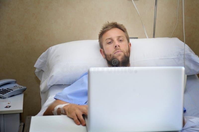 Ung man i sjukhusrum i säng genom att använda internet som forskar information på hans egen skadasjukdom eller sjukdom arkivbild