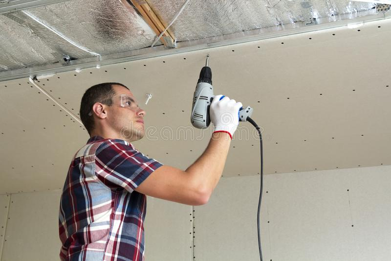 Ung man i skyddsglasögon som fixar det inställda taket för drywall till metallramen genom att använda den elektriska skruvmejseln arkivbild