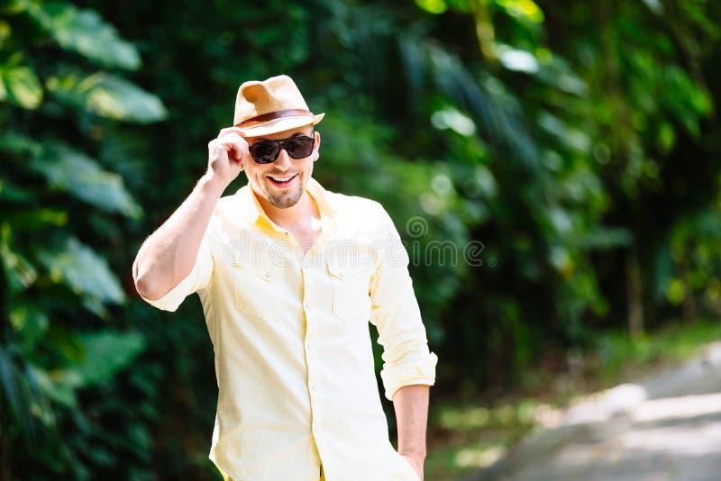 Ung man i solglasögon som bär den gula hatten och tillfällig kläder som har gyckel i solig dag tropisk bakgrund royaltyfria foton