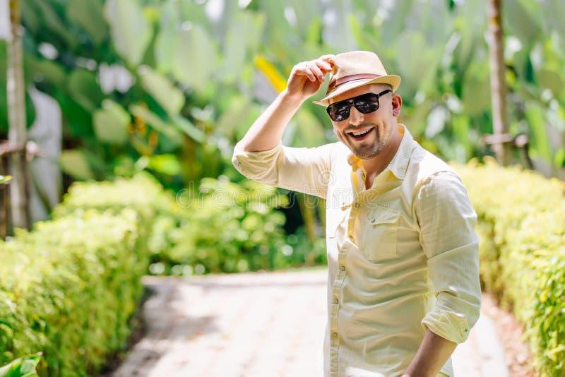 Ung man i solglasögon som bär den gula hatten och tillfällig kläder som har gyckel i solig dag tropisk bakgrund royaltyfri foto