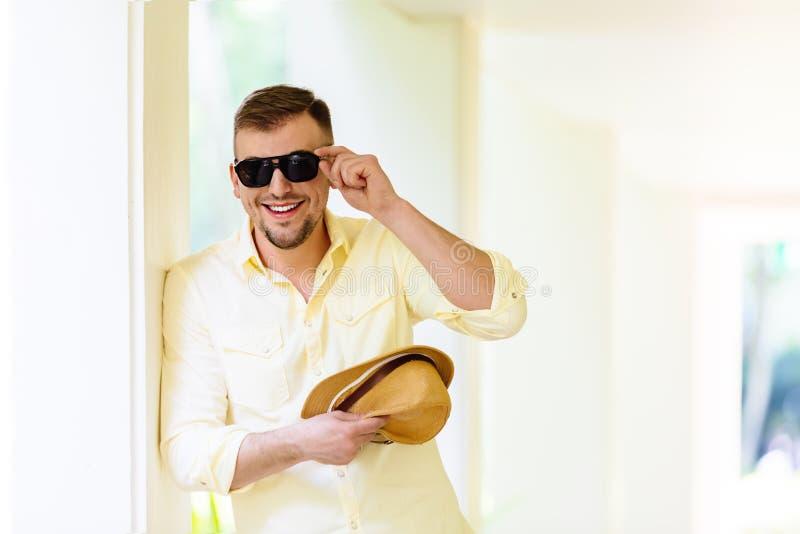 Ung man i solglasögon som bär den gula hatten och tillfällig kläder som har gyckel i solig dag tropisk bakgrund arkivbilder