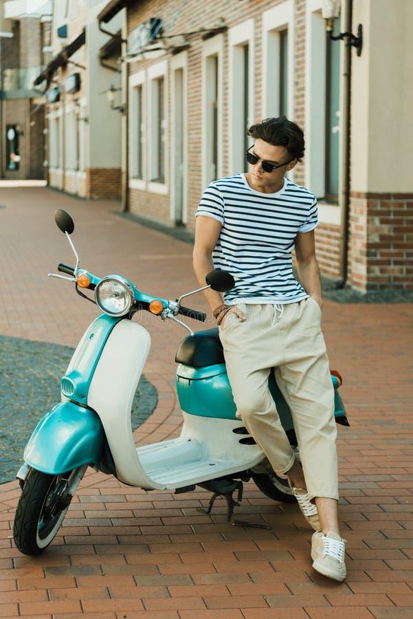 Ung man i solglasögon som lutar på sparkcykeln och bort ser royaltyfri fotografi
