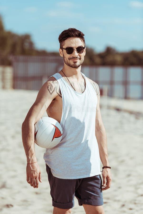 Ung man i solglasögon som rymmer volleybollbollen på stranden arkivfoton