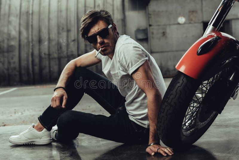 Ung man i solglasögon som sitter nära mopeden och att röka royaltyfria foton