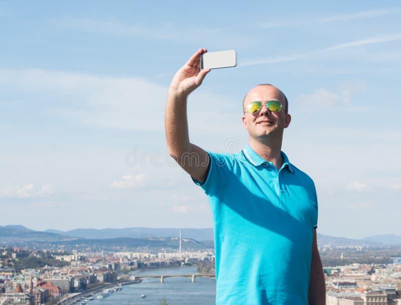 Ung man i solglasögon som tar selfie arkivbild