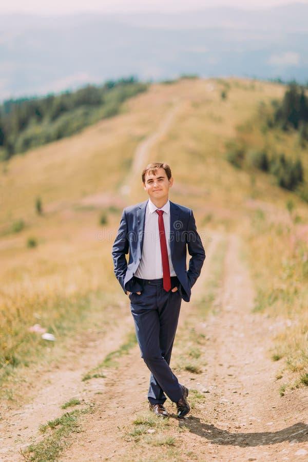Ung man i stilfullt dräktanseende på slinga till och med sommarfält med kullar på bakgrund royaltyfri fotografi