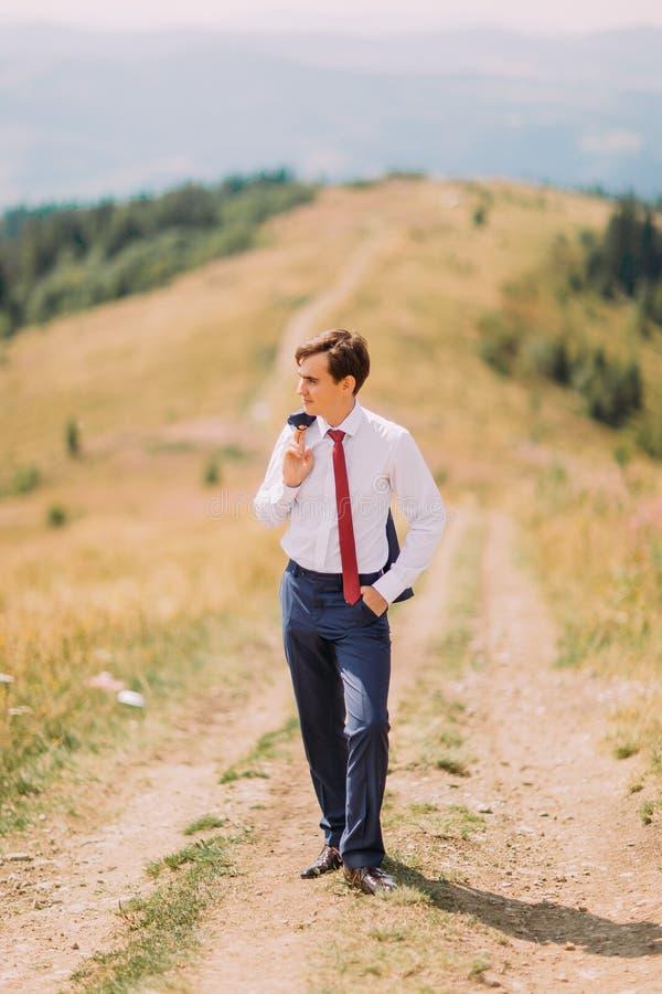 Ung man i stilfullt dräktanseende på vägen på sommarfältet med hans blazer över skuldra fotografering för bildbyråer