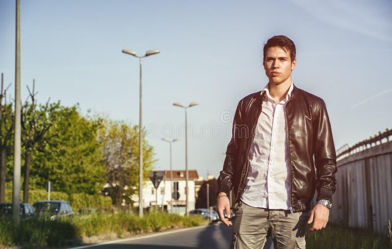 Ung man i svart promenera för läderomslag royaltyfri fotografi