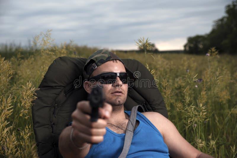 Ung man i svarta exponeringsglas och ett lock av en skyddande färg som siktar med en rak pistol framåt royaltyfria bilder