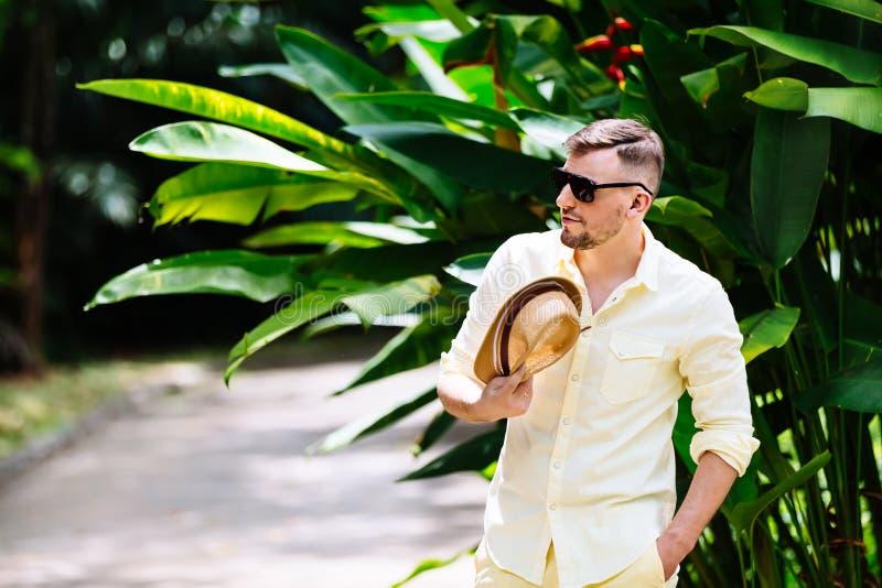 Ung man i tillfällig kläder för solglasögon som rymmer ylellowhatten i händer som har gyckel i solig dag tropisk bakgrund royaltyfri fotografi