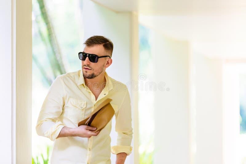 Ung man i tillfällig kläder för solglasögon som rymmer ylellowhatten i händer som har gyckel i solig dag tropisk bakgrund royaltyfri bild