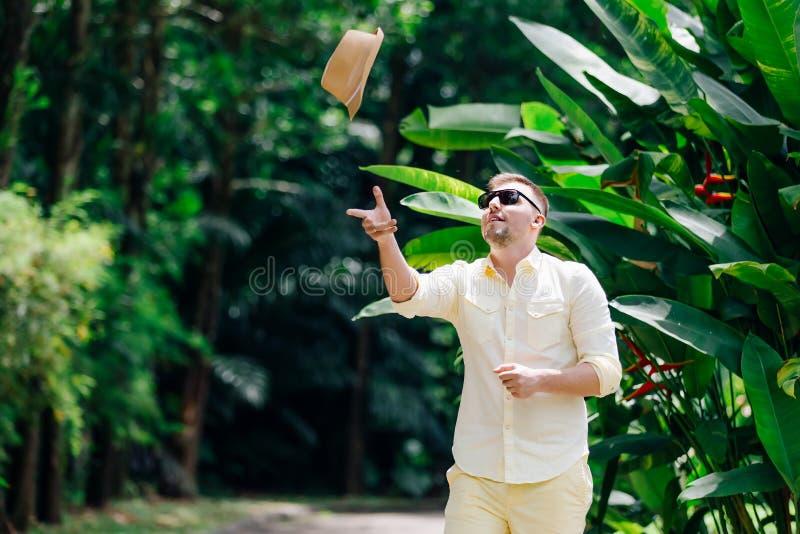 Ung man i tillfällig kläder för solglasögon som throuing ylellowhatten och att ha gyckel i solig dag tropisk bakgrund arkivfoton