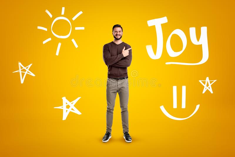 Ung man i tillfällig kläder som står med vikta armar, en hand som pekar för att betitla glädje på gul bakgrund med handen royaltyfri fotografi