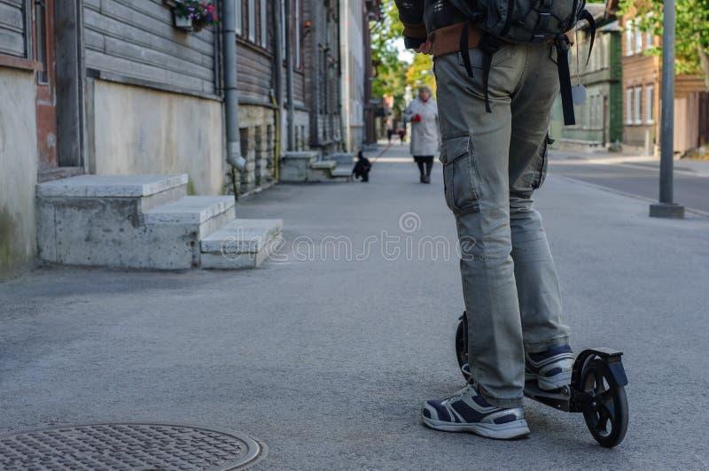 Ung man i tillfälliga kläder på sparksparkcykeln på gatan royaltyfri bild