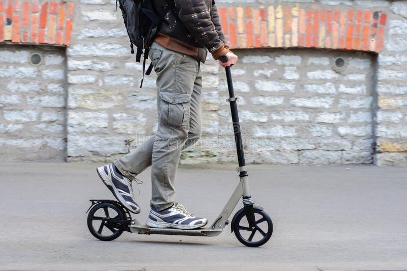 Ung man i tillfälliga kläder på sparksparkcykeln på gatan arkivfoto