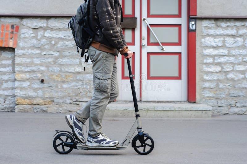 Ung man i tillfälliga kläder på sparksparkcykeln på gatan arkivfoton
