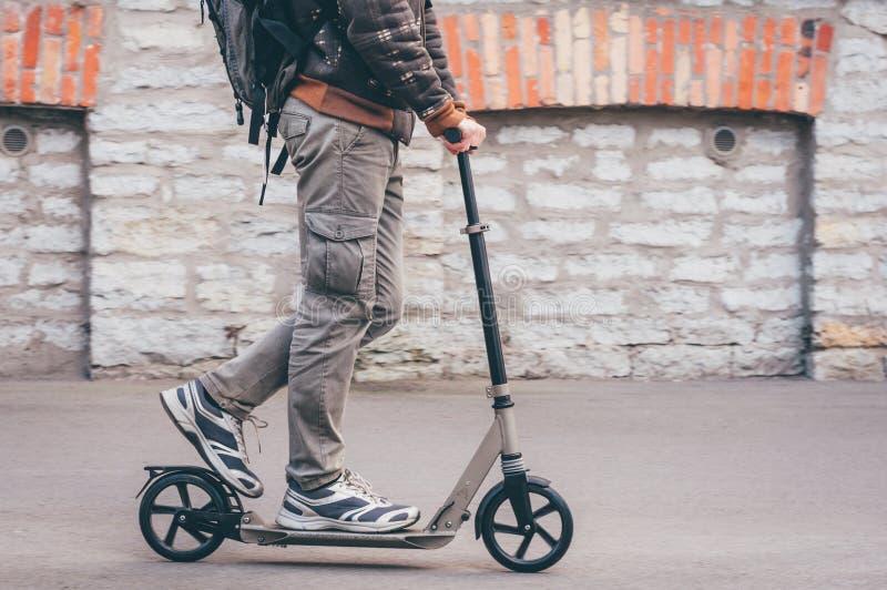 Ung man i tillfälliga kläder på sparksparkcykeln på gatan royaltyfri foto