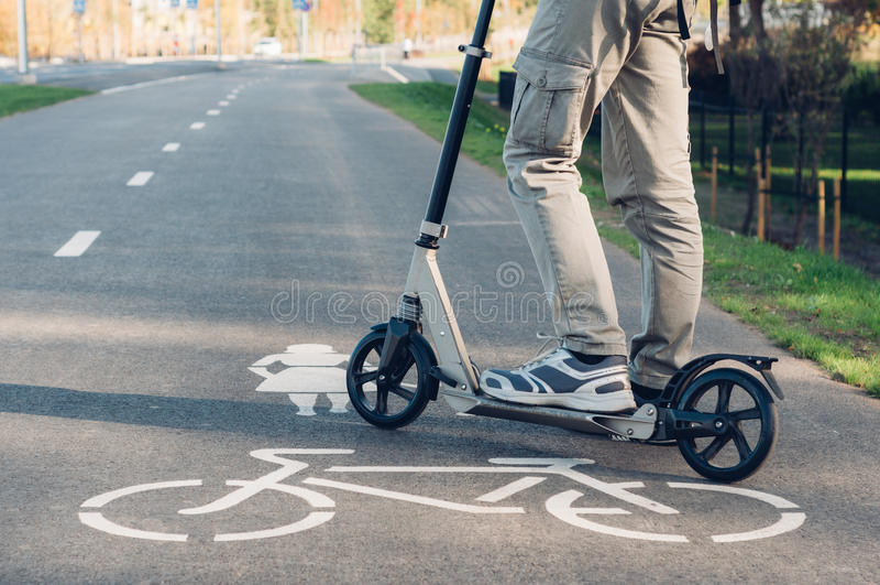 Ung man i tillfälliga kläder på sparksparkcykeln på gatan royaltyfri fotografi