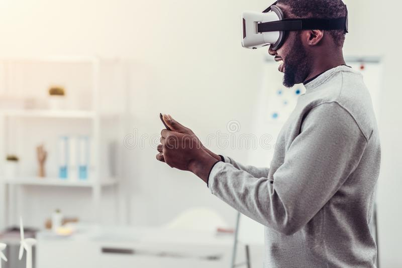 Ung man i tillfälliga spela virtuell verklighetlekar arkivfoton