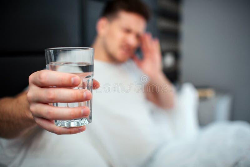 Ung man i underlag Han rymmer exponeringsglas av vatten och visar det till kameran Modellera hållhanden på pannan Huvudvärk eller arkivfoto