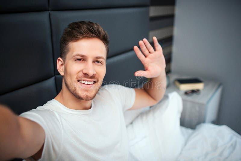 Ung man i underlag Han rymmer kameran och leende Grabbvåg med handen fotografering för bildbyråer