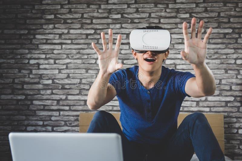 Ung man i virtuell verklighethörlurar med mikrofon eller exponeringsglas som 3d spelar videoen fotografering för bildbyråer