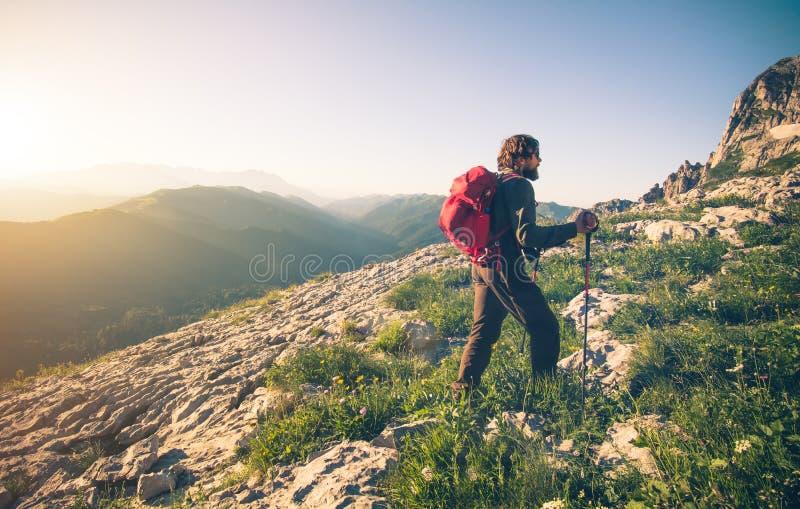 Ung man med att klättra i berg för ryggsäck som är utomhus- arkivfoton