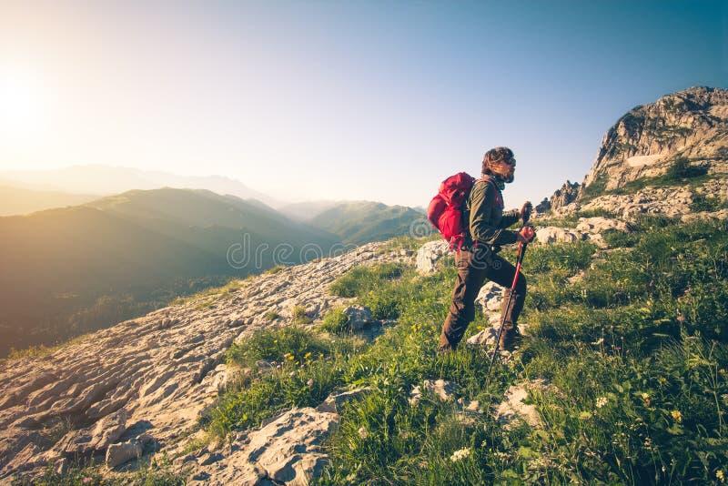 Ung man med att klättra i berg för ryggsäck som är utomhus- royaltyfria foton