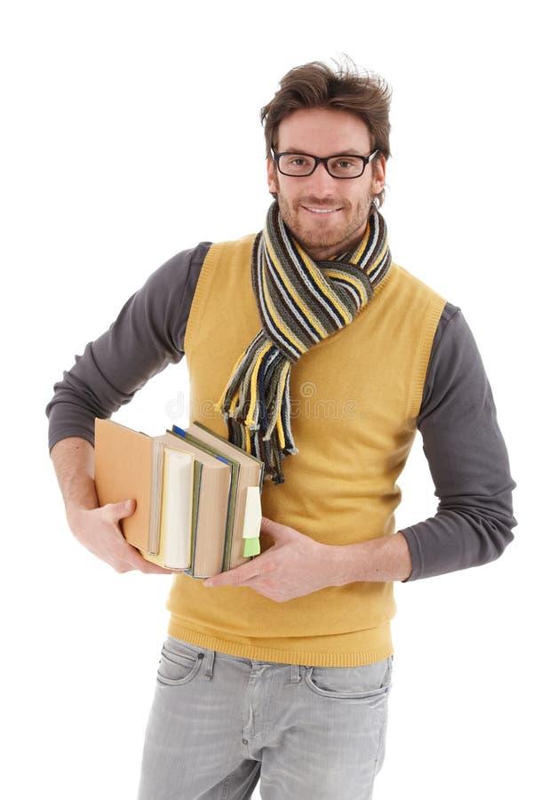 Ung man med att le för böcker royaltyfri fotografi