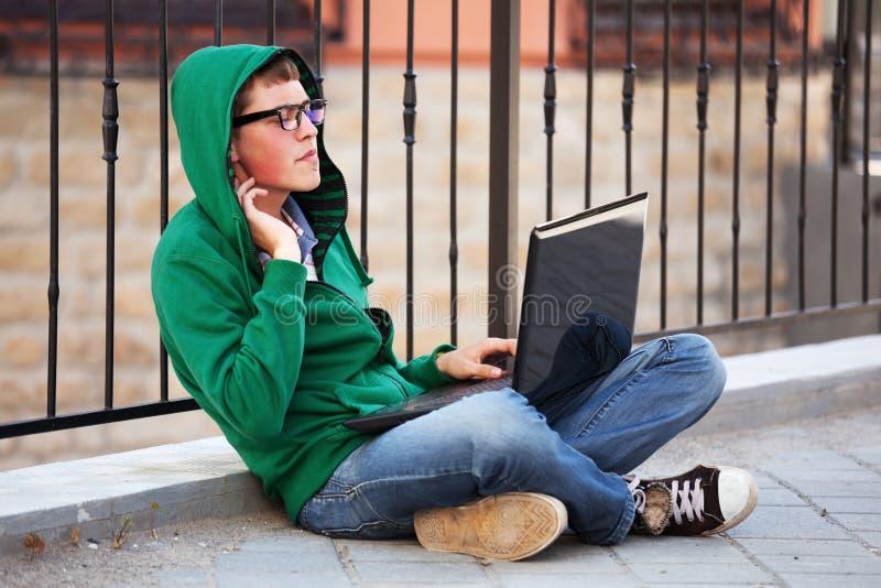 Ung man med bärbar dator royaltyfria bilder