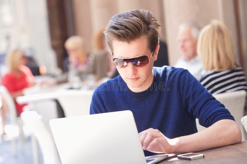 Ung man med bärbar datorsammanträde i utvändigt kafé arkivfoto