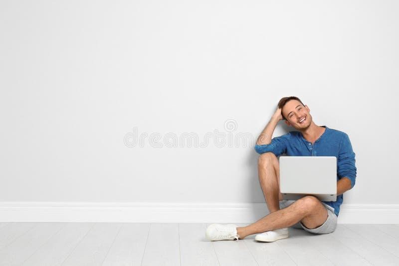 Ung man med bärbar datorsammanträde på golv mot den ljusa väggen royaltyfri bild