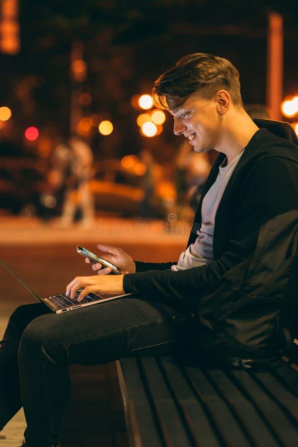 Ung man med bärbara datorn i nattstad royaltyfri foto