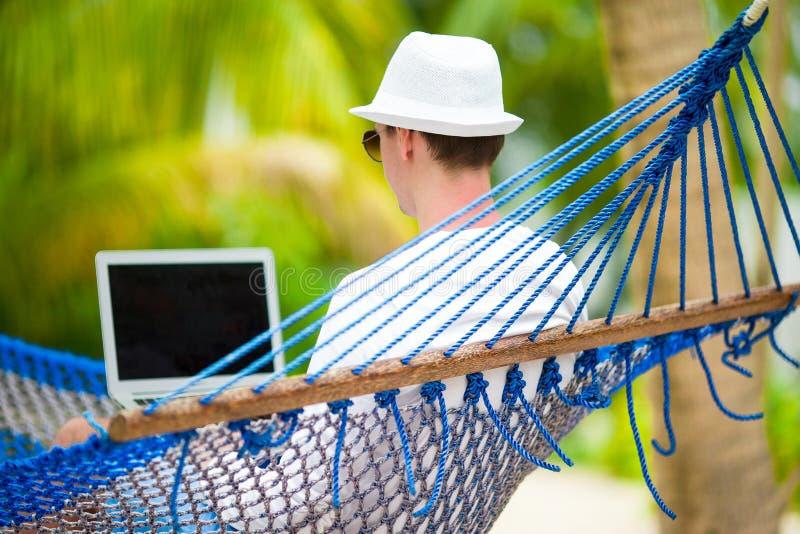 Ung man med bärbara datorn på hängmattan på tropisk semester arkivbilder