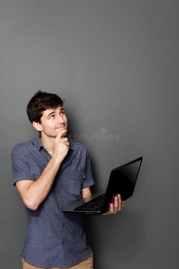 Ung man med bärbara datorn som upp till ser kopieringsutrymme royaltyfri bild