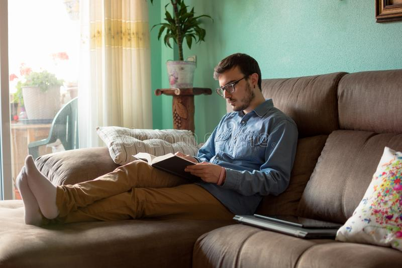 Ung man med boken på soffan hemma royaltyfria foton