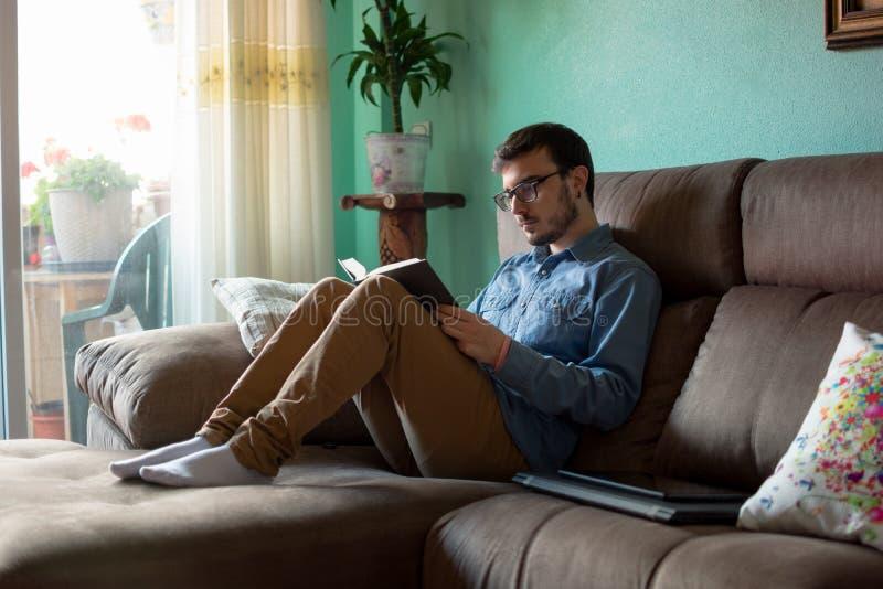 Ung man med boken p? soffan hemma arkivfoto