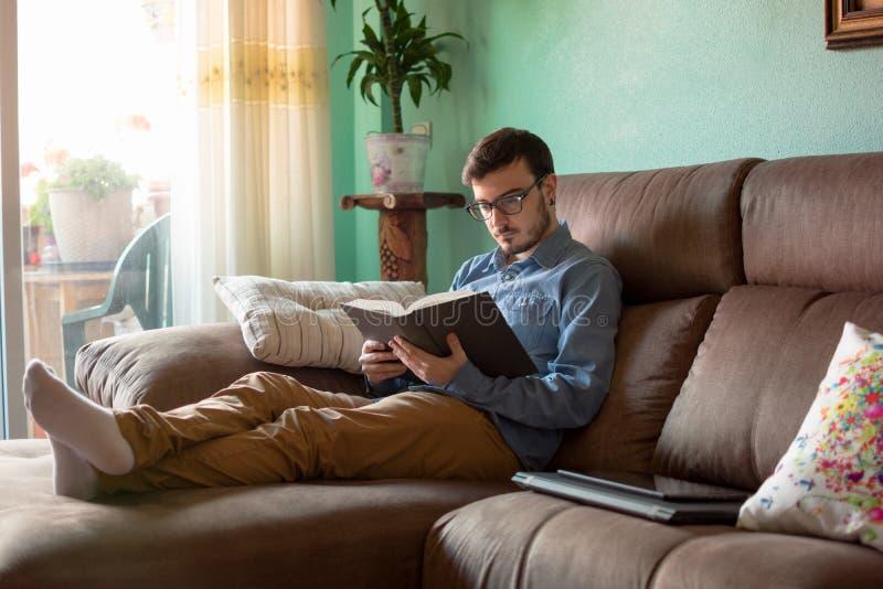 Ung man med boken p? soffan hemma royaltyfria bilder