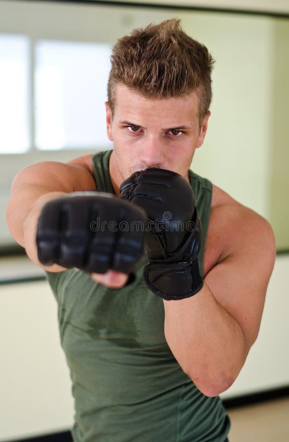 Ung man med boxares handskar som kastar stansmaskin in mot kamera royaltyfria bilder