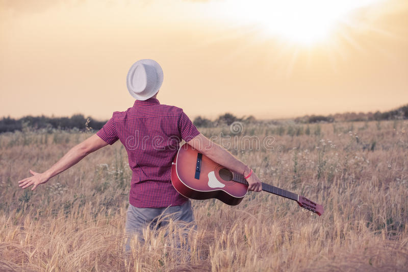 Ung man med den akustiska gitarren som tycker om solnedgången royaltyfri bild