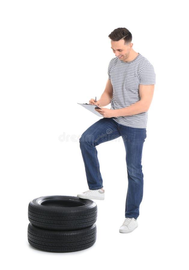 Ung man med den bilgummihjul och skrivplattan royaltyfri bild