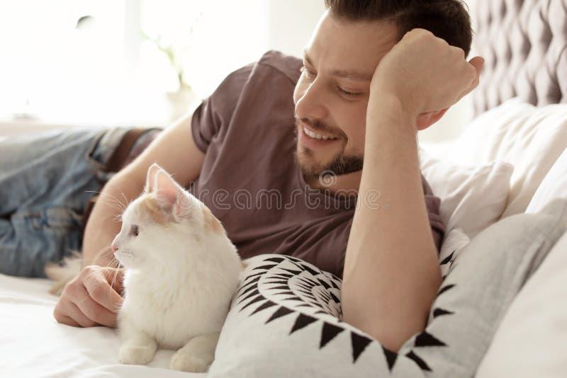 Ung man med den gulliga katten på säng arkivfoton