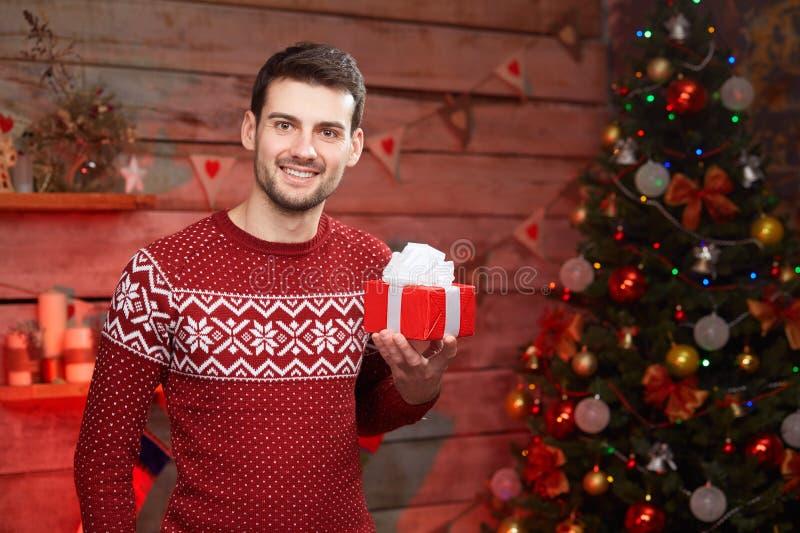 Ung man med den slågna in lilla röda gåvaasken för jul royaltyfri fotografi