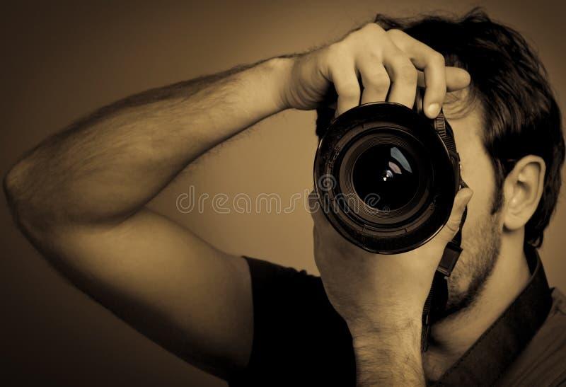 Ung man med den yrkesmässiga kameran royaltyfri foto