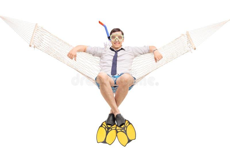 Ung man med dykningfena som ligger i en hängmatta arkivfoton