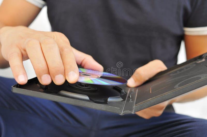 Ung man med en DVD eller en CD fotografering för bildbyråer