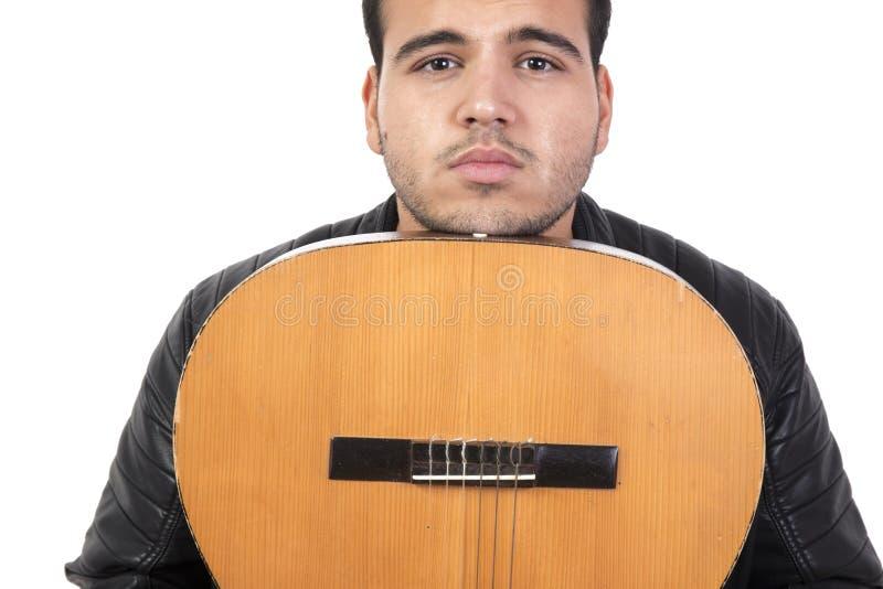 Ung man med en gammal akustisk gitarr fotografering för bildbyråer