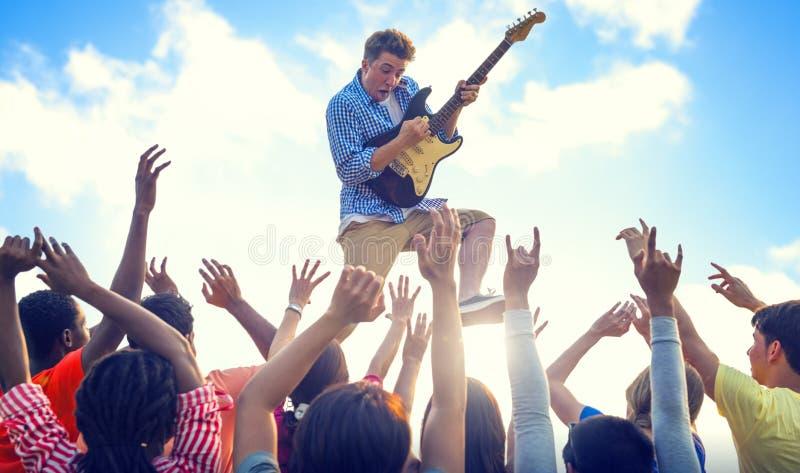 Ung man med en gitarr som utför på extatiska folkmassor arkivfoton