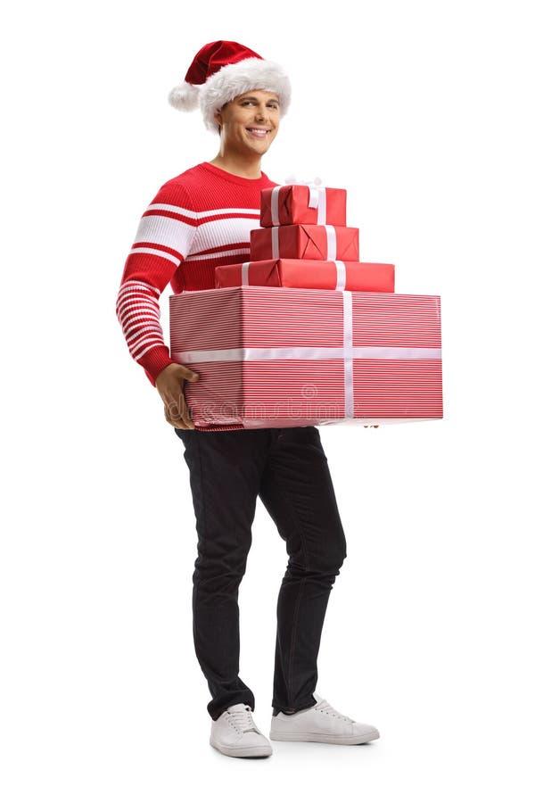 Ung man med en julsanta hatt som rymmer en h?g av g?vor royaltyfria bilder