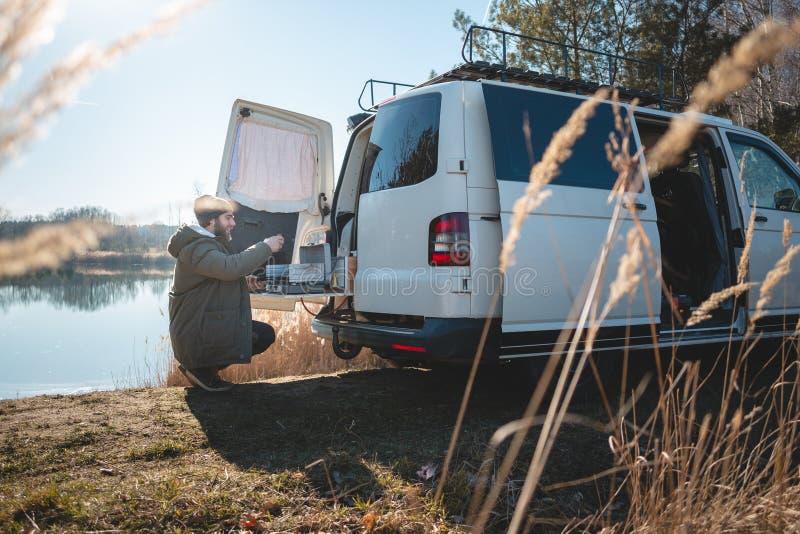Ung man med en konverterad skåpbil på en sjö i natur arkivfoto